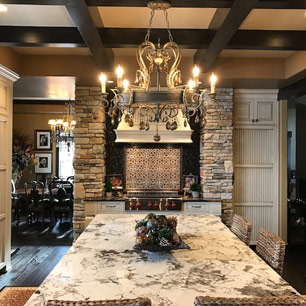 Kitchen Island featuring granite, chandelier, wood beams, custom cabinets and tile