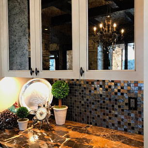 Kitchen featuring antique mirror, marble, custom cabinets and glass tile