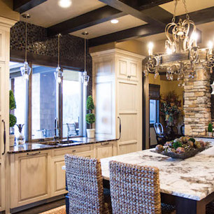 Kitchen featuring wood flooring, granite, marble, chandelier and pendant lighting, wood beams, custom cabinets and tile