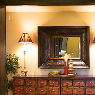 Hallway setting with chests, lamp lighting and mirror