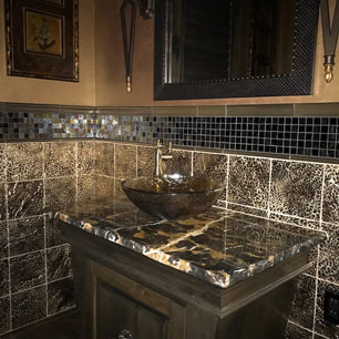 Powder Room featuring marble, custom cabinetry, metallic paint, glass tile, animal print tile, sconce and chandelier lighting and porcelain tile flooring