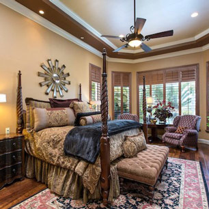 Master Bedroom with wood flooring, luxury bedding, area rug, bench, seating and lamp lighting